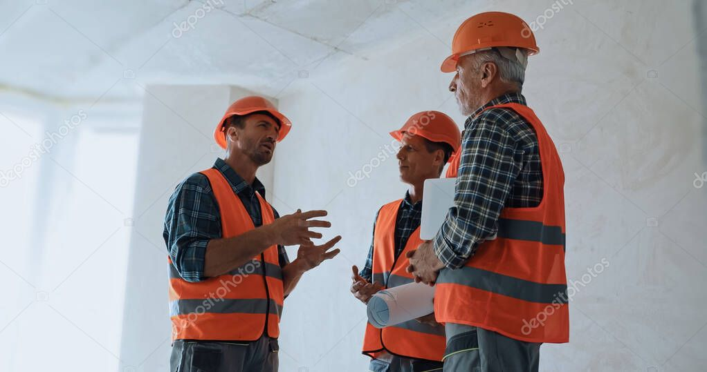 Builder gesturing while talking with coworkers in hard hats on construction site stock vector