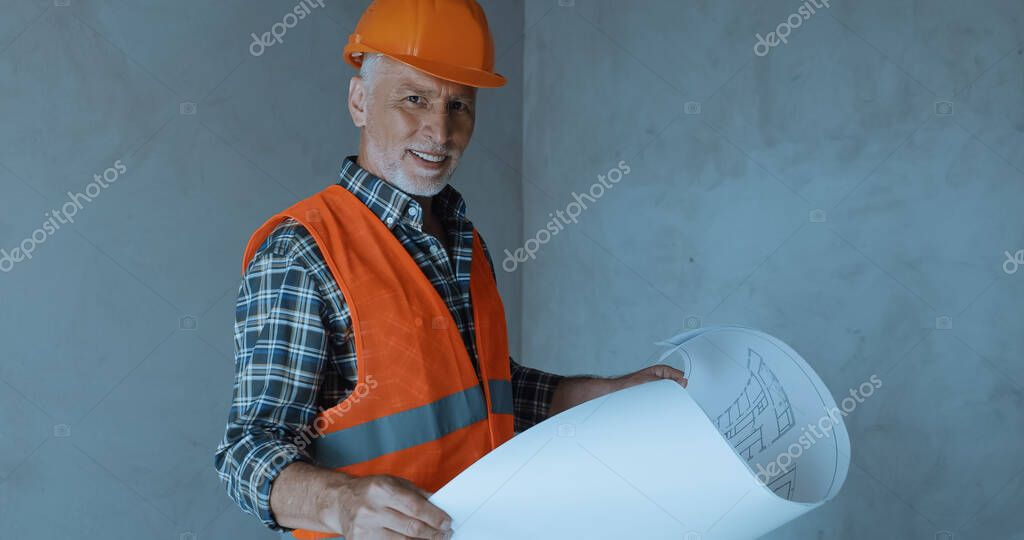 Happy builder holding blueprint and smiling on construction site stock vector
