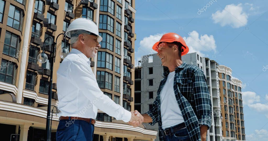 Mature engineer and builder shaking hands and talking on construction site stock vector