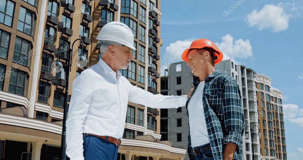 Mature engineer touching shoulder of builder on construction site stock vector