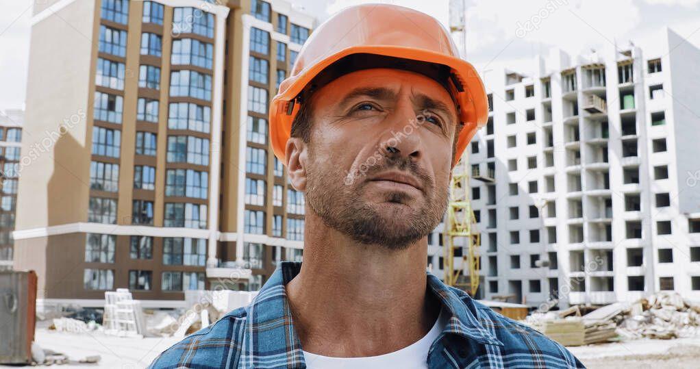 Handsome builder looking away on construction site stock vector