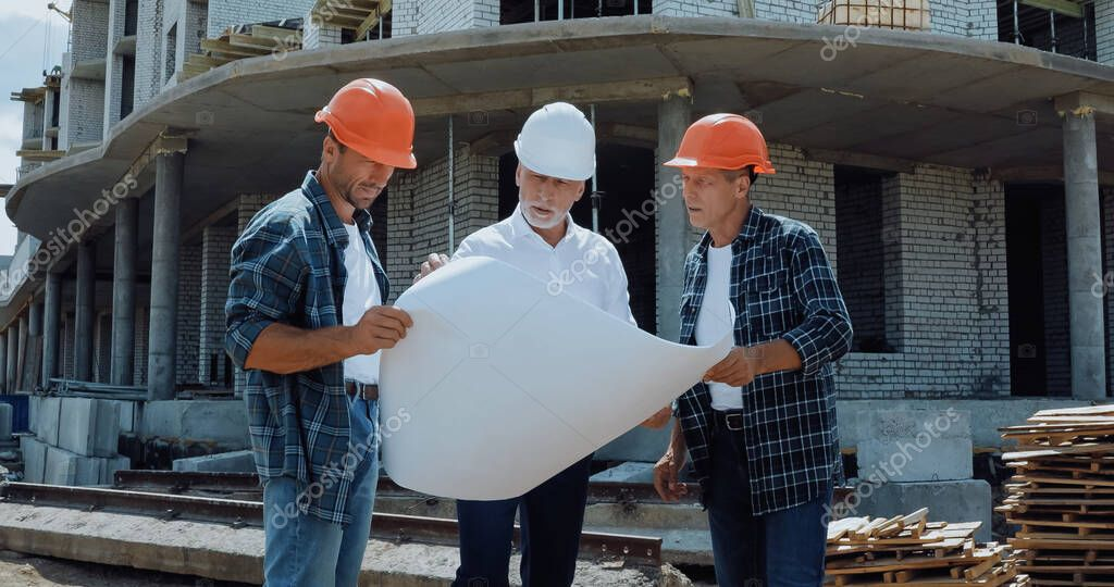 Engineer and builders in hard hats discussing blueprint on construction site stock vector