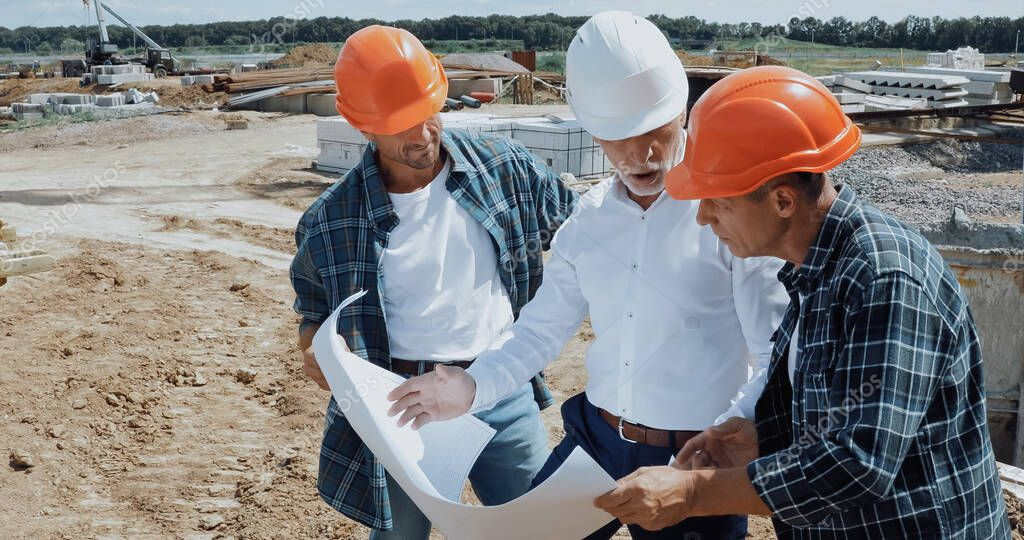 Engineer and builders talking and looking at blueprint on construction site stock vector
