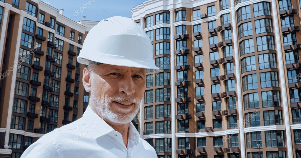 Middle aged engineer looking at camera while smiling near building on background stock vector