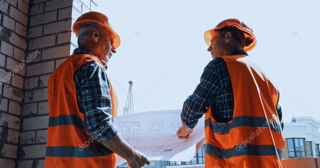 Low angle view of builders in safety vests with blueprint talking on construction site stock vector