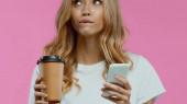 töprengő nő használ okostelefon és a gazdaság kávé menni elszigetelt rózsaszín