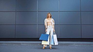 Binanın yanında alışveriş torbalarıyla duran uzun boylu bir kadın.