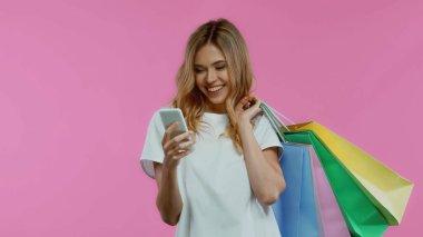 Akıllı telefon kullanan mutlu bir kadın ve mor renkte izole edilmiş alışveriş torbaları tutan.