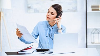 Young call center operator looking at document while working in office stock vector