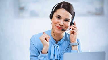 Joyful call center operator smiling at camera while working in office stock vector