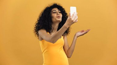 Pregnant hispanic woman blowing air kiss during video call on smartphone isolated on yellow stock vector