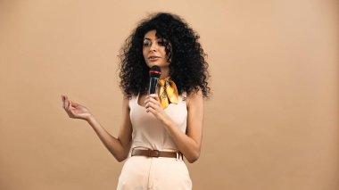 hispanic woman holding microphone isolated on beige