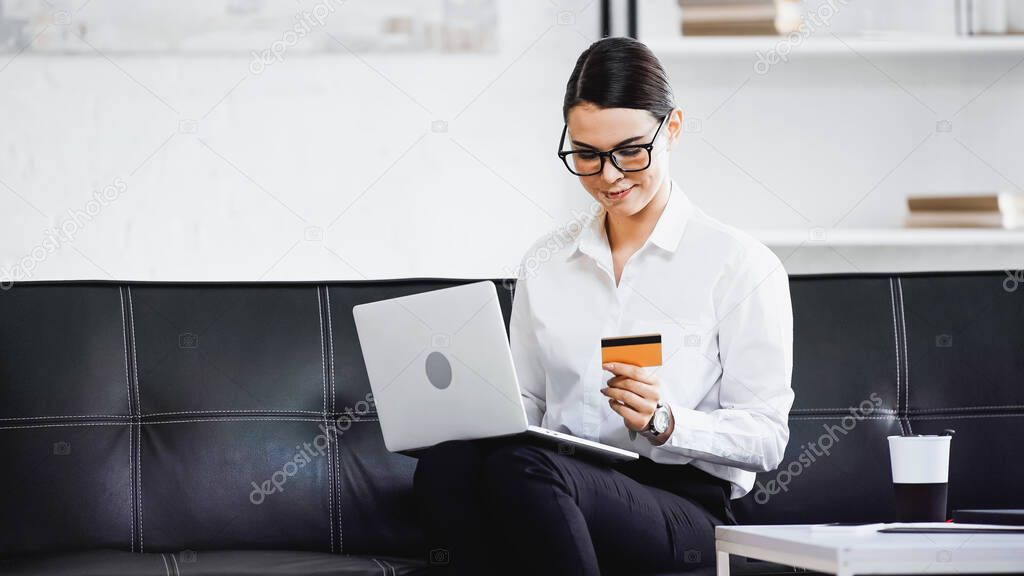 Young businesswoman sitting on couch with laptop and credit card stock vector