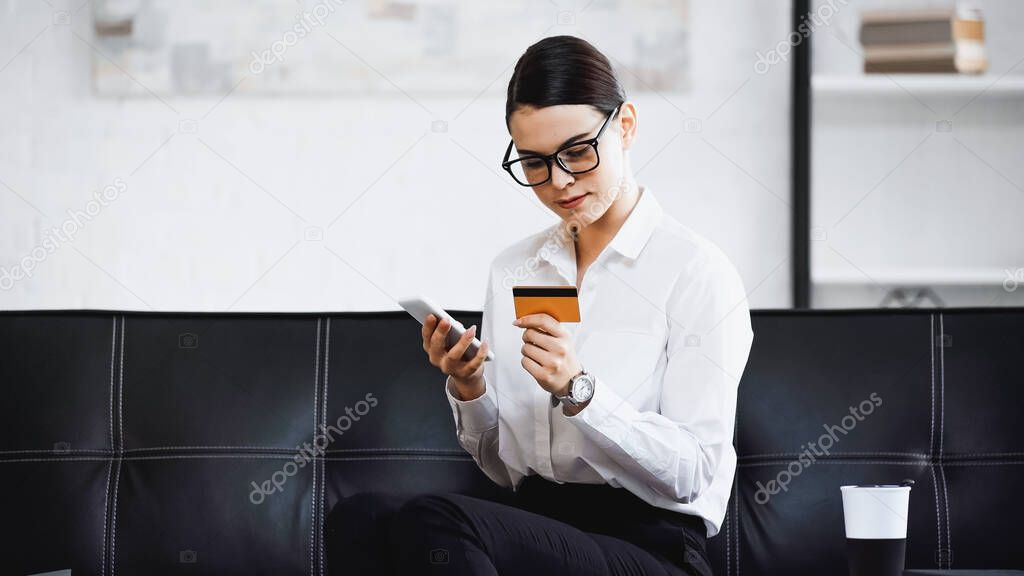Pretty businesswoman sitting on sofa with cellphone and credit card stock vector