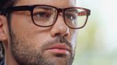 zblízka vousatý podnikatel v brýlích dívá pryč
