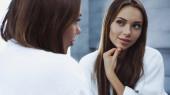 mladá a hezká žena v županu při pohledu do zrcadla
