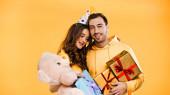 boldog barát és barátnő ajándékokkal ölelés elszigetelt sárga
