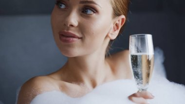 Close up of happy woman holding glass of champagne while taking bath with foam in bathtub stock vector