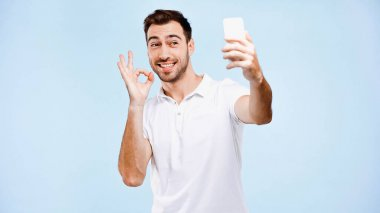 Smiling man taking selfie and showing okay sign isolated on blue stock vector