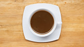 top view of hot chocolate drink in white cup on wooden surface