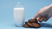 částečný pohled na muže, jak si bere čokoládové sušenky u skla s čerstvým mlékem