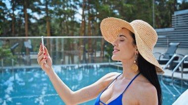 Happy brunette woman in straw hat taking selfie near pool stock vector
