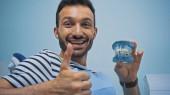 radostný muž ukazuje palec nahoru, zatímco drží zuby model v zubní klinice