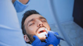 dentist in medical mask curing teeth of patient with dental drill, blurred foreground