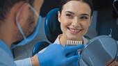 zubař ukazující prstem na paletu barev zubů v blízkosti usmívající se ženy, rozmazané popředí