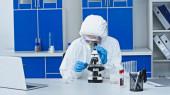 Wissenschaftler im Schutzanzug arbeiten im Labor unter dem Mikroskop