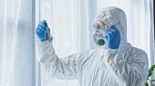 Wissenschaftler im Schutzanzug spricht auf Smartphone, während er Reagenzglas mit Blutprobe in der Hand hält