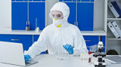 Virologe im Warnanzug arbeitet am Laptop im Labor