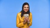 Veselá mladá žena drží dolarové bankovky izolované na modré