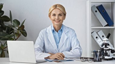 Happy doctor smiling at camera while sitting near laptop at workplace stock vector