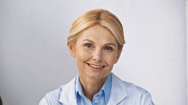 Mature, blonde doctor smiling at camera in hospital stock vector