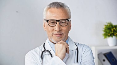 Mature doctor in eyeglasses smiling at camera in clinic stock vector