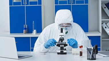 Virologist in hazmat suit doing working with microscope near laptop in laboratory stock vector