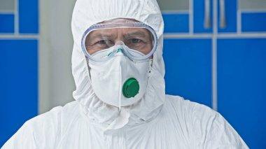 Scientist in hazmat suit looking at camera in laboratory stock vector
