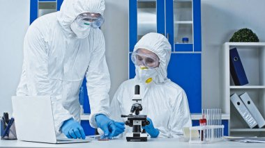 Scientist in hazmat suit showing blood sample to colleague near microscope stock vector