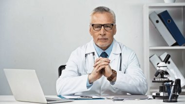 Doctor in eyeglasses sitting near laptop and looking at camera stock vector
