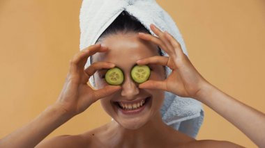 Cheerful woman covering eyes with cucumber slices isolated on beige stock vector