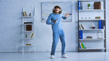 full length view of young businessman in wireless headphones dancing in modern office