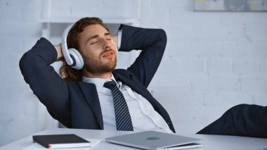 smiling businessman listening music in wireless headphones while resting in office