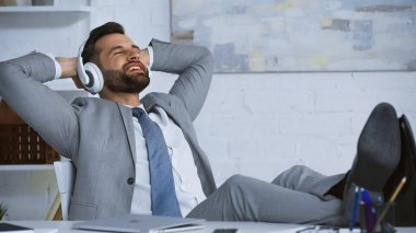 happy businessman listening music in headphones while relaxing in office