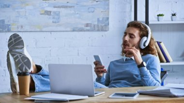 young businessman listening music and chatting on smartphone while relaxing in office