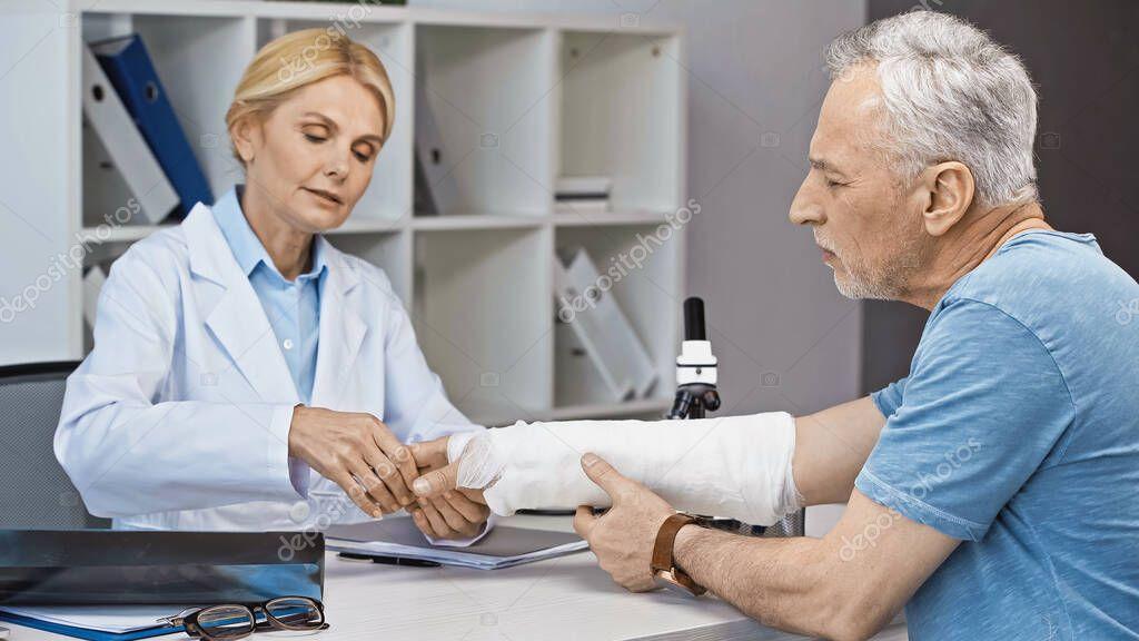 Traumatologist examining broken arm of mature man in hospital stock vector