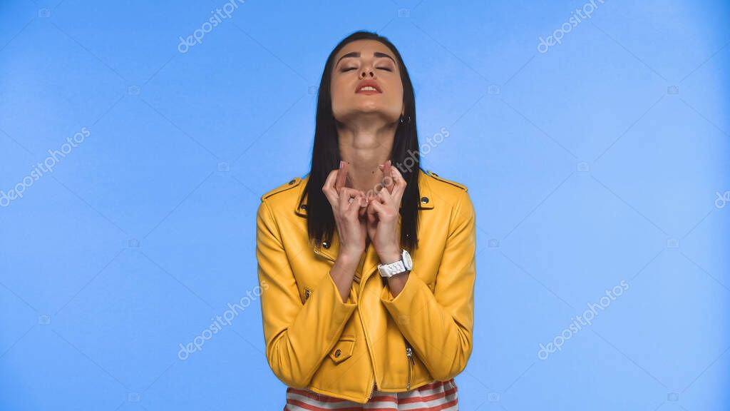 Young woman with crossed fingers and closed eyes isolated on blue stock vector
