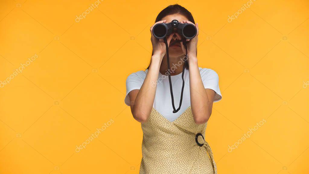 Woman looking through binoculars isolated on yellow stock vector