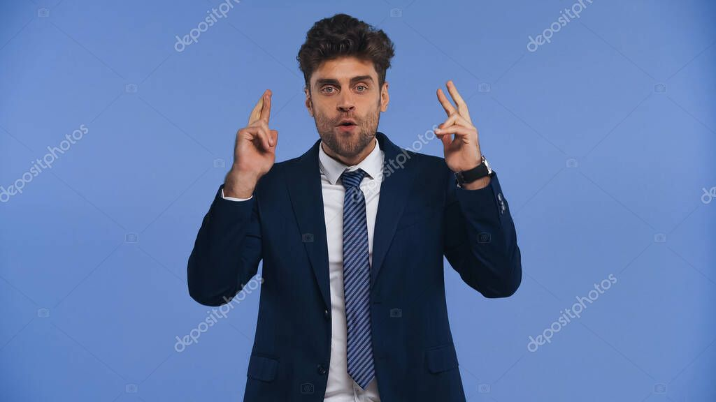 Amazed businessman with crossed fingers looking at camera isolated on blue stock vector
