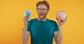 glücklich Rotschopf Mann hält Sparschwein und Bargeld isoliert auf gelb